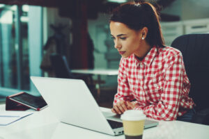 Woman in red and white plaid button down shirt researching breast augmentation options on her office computer.
